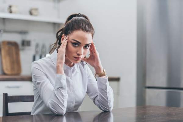 Upset woman in white blouse sitting at table and putting hands forehead in kitchen, grieving disorder concept